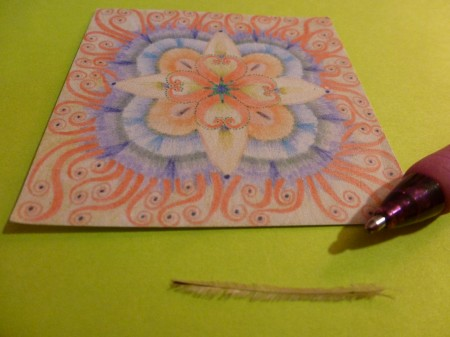 For some perspective, here is the feather next to a pen. (I added my mandala for color.)